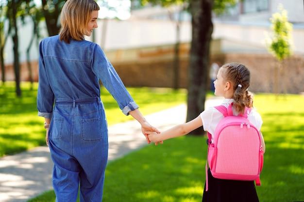Mère mène une petite écolière enfant en première année