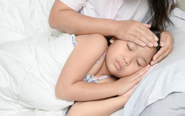 Mère mesurant la température d'un enfant malade.