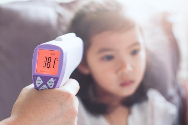 Mère, mesurer, température, elle, malade, asiatique, petite fille, enfant, à, infrarouge, thermomètre