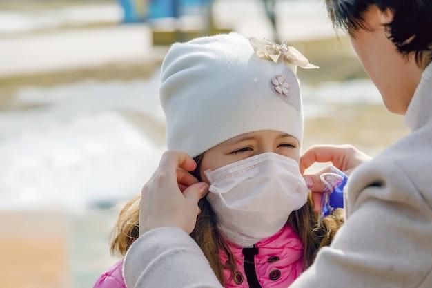 La mère met un masque médical de protection pour sa fille contre le virus, protégeant l'enfant contre le virus avec un masque médical, protégeant contre le coronavirus, covid-19