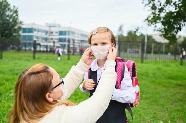 La mère met un masque de sécurité sur le visage de sa fille. écolière prête à aller à l'école.