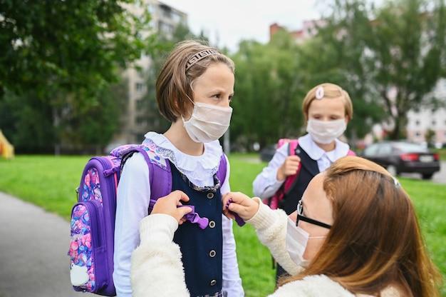 La mère met un masque de sécurité sur le visage de sa fille. les écolières sont prêtes à aller à l'école.