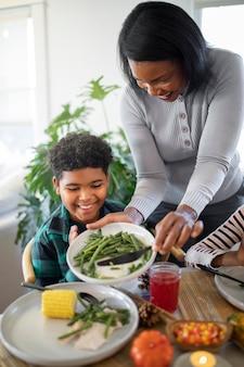 Mère mettant de la nourriture pour le jour de thanksgiving pour son fils