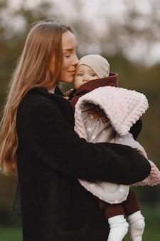 Mère à la mode avec sa fille. les gens marchent dehors. femme dans une veste noire.