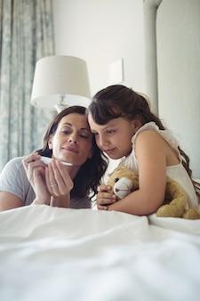 Mère montrant la température sur un thermomètre à sa fille