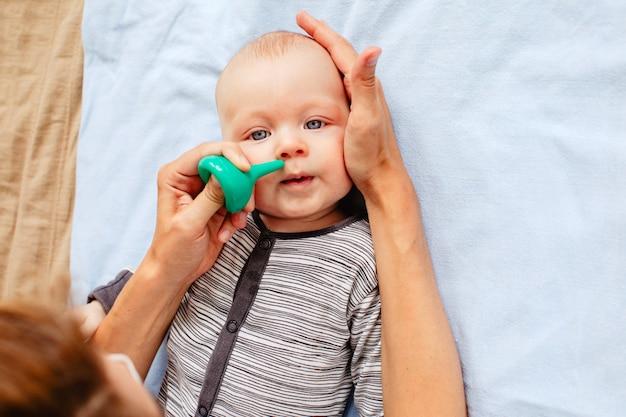 Mère nettoyant le nez de bébé mignon