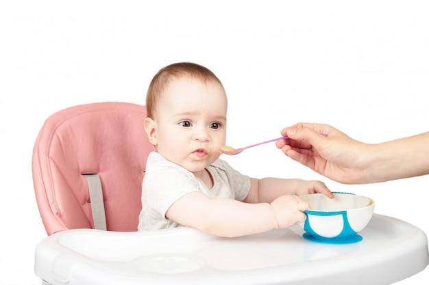 Mère nourrir sa mignonne petite fille sur chaise isolé sur fond blanc.