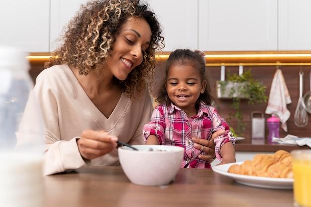 Mère nourrissant sa fille dans la cuisine