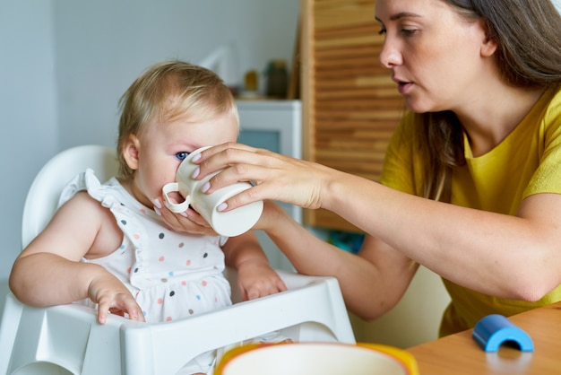 Mère nourrissant sa fille avec du lait maternisé dans une tasse d'aliments sains pour la garde d'enfants