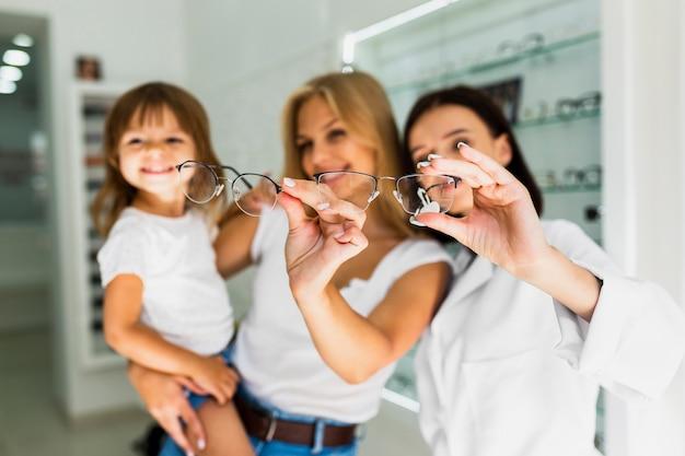 Mère et opticien tenant des montures de lunettes