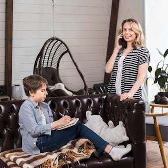 Mère parlant au téléphone pendant que son fils fait ses devoirs