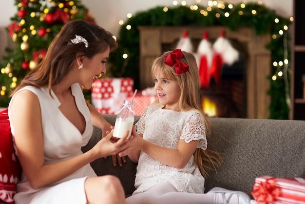 Mère passant bouteille de lait à sa fille