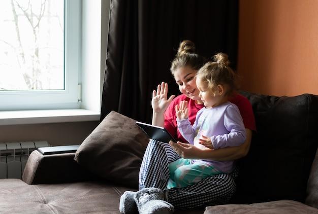 Mère et pâtissier bavardant, passer un appel vidéo, sur tablette à la maison. petite fille agite sa main à l'écran.