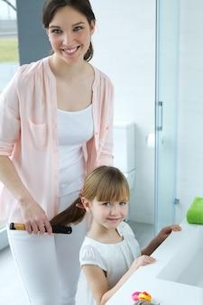 Mère peignant sa fille dans la salle de bain