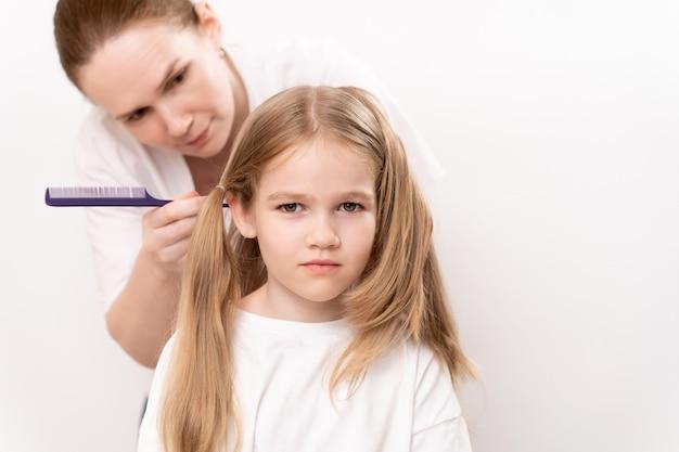La mère peigne et coiffe une petite fille sur fond blanc. maman est coiffeuse. économiser de l'argent dans un salon de beauté. shampooings et cosmétiques pour les cheveux des enfants.