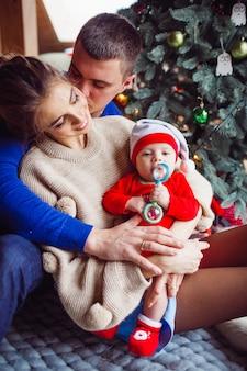 La mère, le père et le bébé assis près de l'arbre de noël