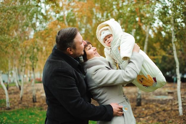 Mère et père avec bébé vêtu de vêtements chauds marchant sur une journée ensoleillée à l'extérieur. une famille heureuse passe du temps ensemble.
