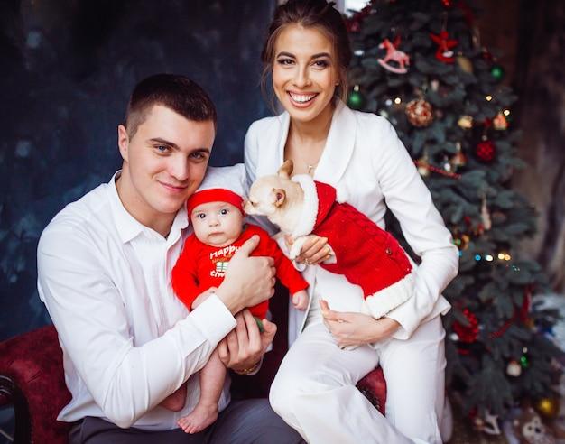 La mère, le père, le chien et le bébé assis près de l'arbre de noël
