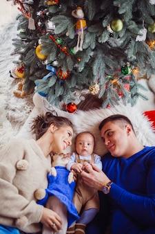 La mère, le père, le chien et le bébé sont allongés sur le sol près de l'arbre de noël
