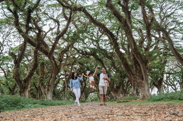 Mère et père et deux enfants sourient en marchant à travers les grands arbres