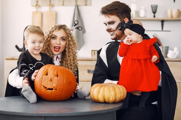 Mère père et enfants en costumes et maquillage. la famille se prépare à la célébration de l'halloween.