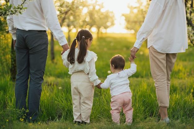 Mère père et filles marchant dans le parc