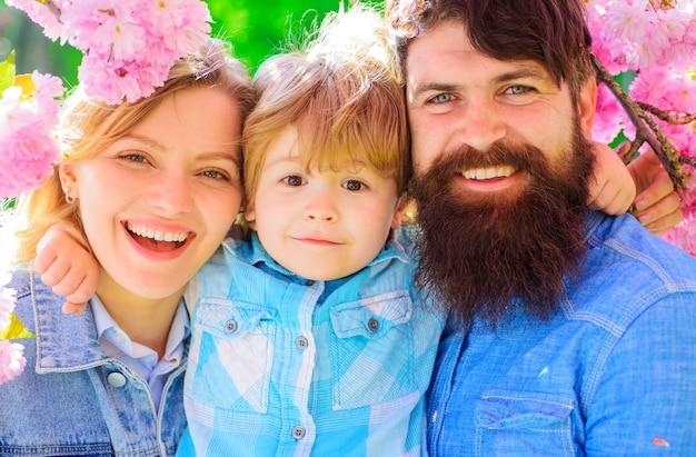 Mère, père et fils ensemble dans le parc de sakura en fleurs, famille heureuse dans le jardin de sakura au printemps, printemps.