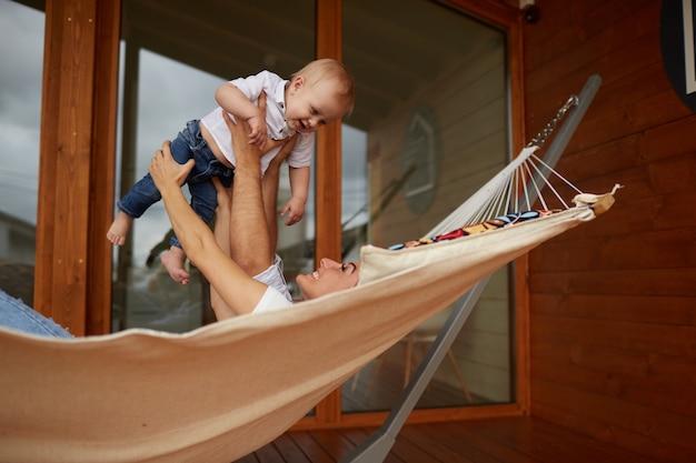 La mère, le père et le fils sont allongés sur le hamac