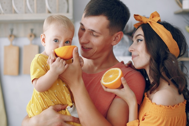 Mère et père nourrissent une orange avec leur fille