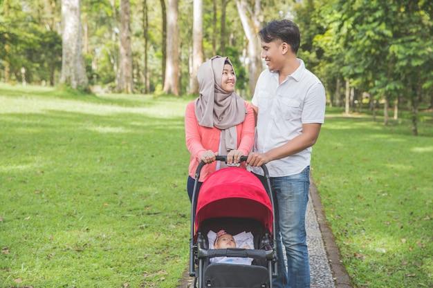 Mère et père poussant la poussette de bébé dans le parc