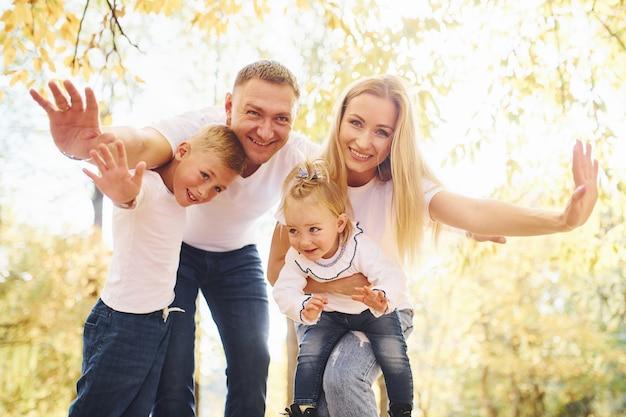La mère et le père tiennent les enfants sur les épaules et dans les mains. une jeune famille joyeuse se promène ensemble dans un parc en automne.