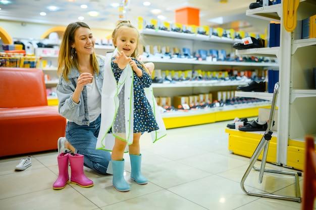 Mère et petit bébé acheter des chaussures dans le magasin pour enfants