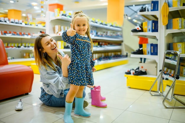 Mère et petit bébé en choisissant des chaussures dans le magasin pour enfants