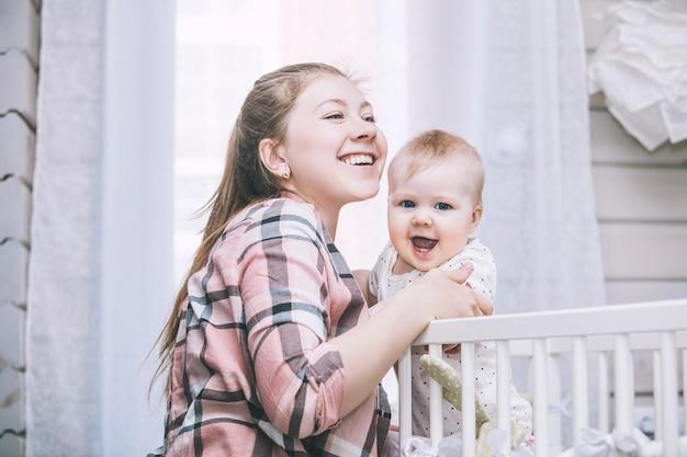 Mère et petit bébé est dans le berceau réveillé le matin et souriant à la maison