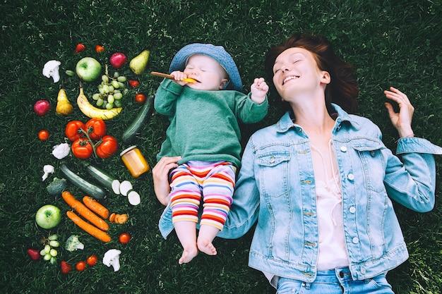 Mère et petit bébé sur l'herbe verte avec cadre de fruits et légumes fraisnutrition saine
