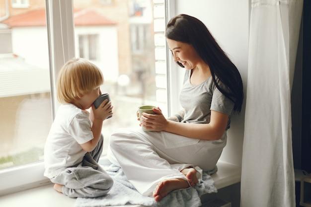 Mère et petit fils assis sur un rebord de fenêtre avec un thé