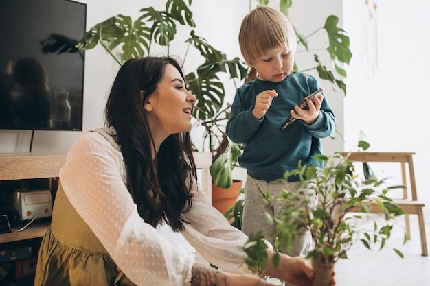 Mère avec petit fils cultivant des plantes à la maison