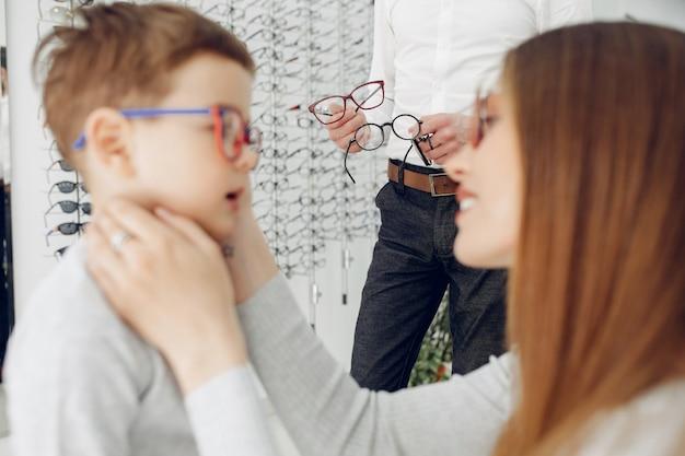 Mère avec petit fils dans le magasin de lunettes