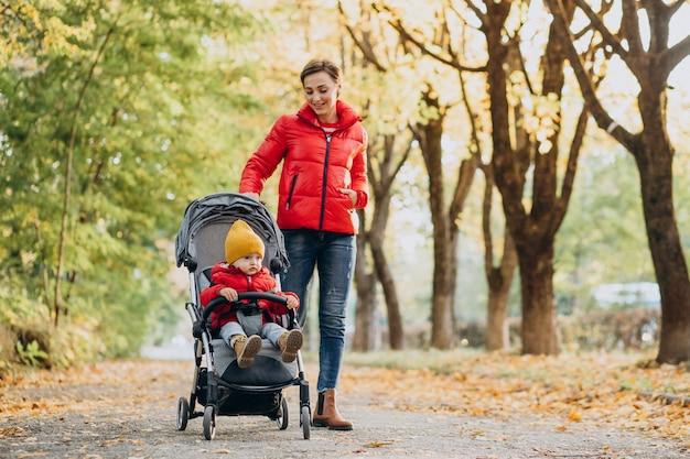 Mère avec petit fils dans la poussette de bébé marchant dans le parc automnal
