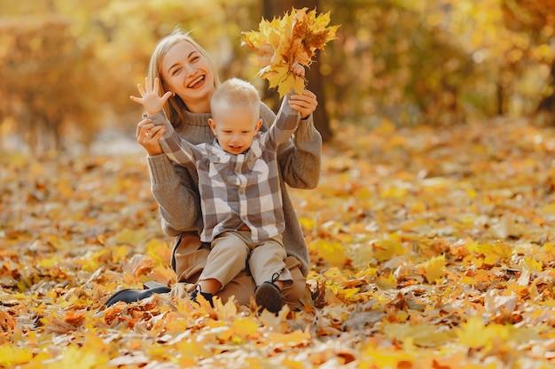 Mère avec petit fils jouant dans un champ d'automne