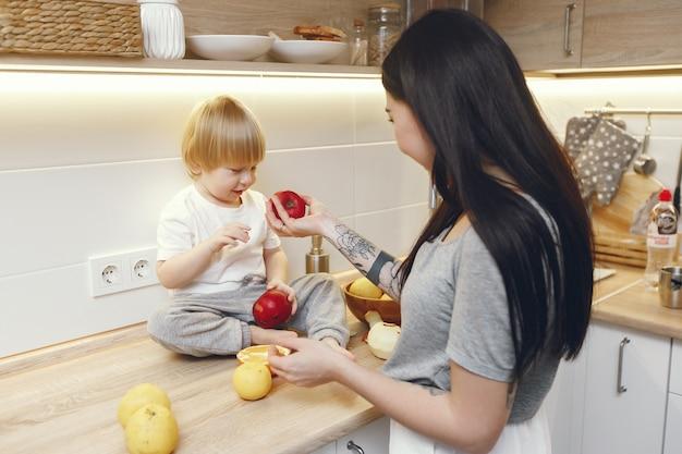 Mère avec petit fils, manger des fruits dans une cuisine