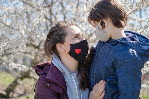 Une Mère Avec Un Petit Fils Portant Des Masques De Protection Est Allée Se Promener De Chez Elle. La Ville Est En Quarantaine. Photo Premium