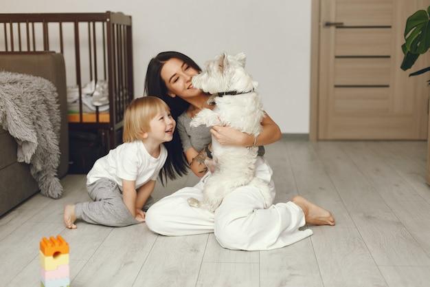 Mère et petit fils s'amusent à la maison avec un chien