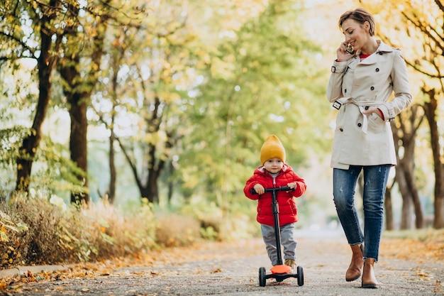 Mère avec petit fils en scooter dans le parc automnal