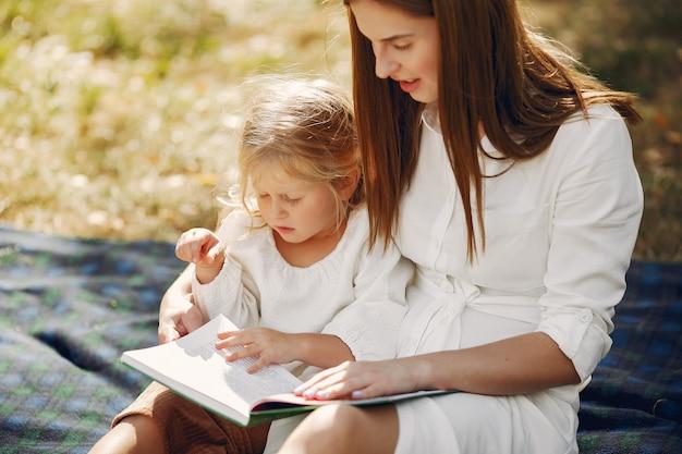 Mère avec petite fille assise sur un plaid et lire le livre