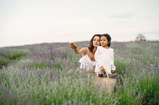 Mère avec petite fille sur champ de lavande. belle femme et bébé mignon jouant dans le champ de prairie. vacances en famille en journée d'été.