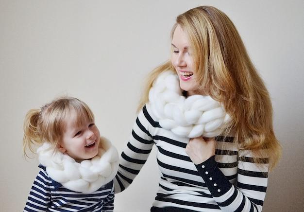 Mère et petite fille en chapeaux et écharpe sur fond blanc, family look