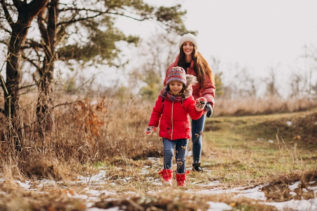 Mère avec petite fille dans une forêt d'hiver