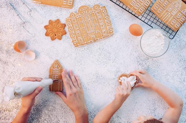 Mère et petite fille décorant les maisons de biscuits de pain d'épice de noël. vue de dessus, pose à plat.