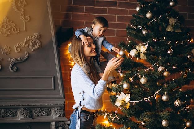 Mère avec petite fille décorer un arbre de noël